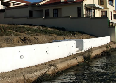 A retainer wall is constructed at the edge of a waterfront plot in Port Owen